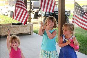 Three little girls waving American flags